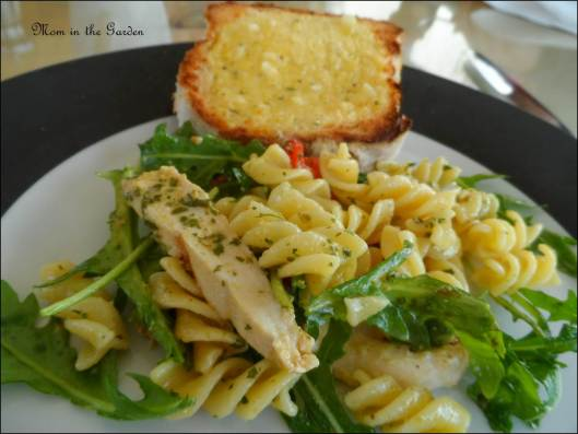Chicken pasta salad with roasted peppers served with garlic bread