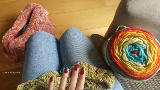 fingers with red nailpolish, rainbow colored yarn