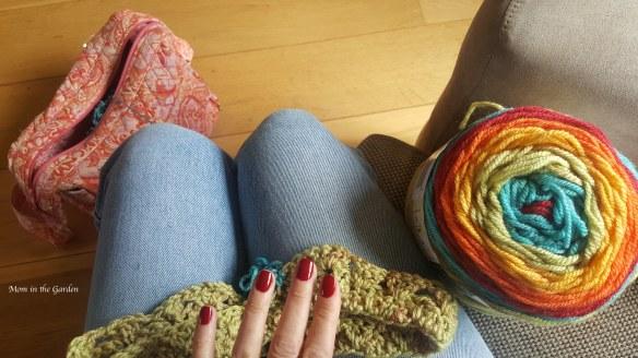 fingers with red nailpolish, rainbow colored yarn
