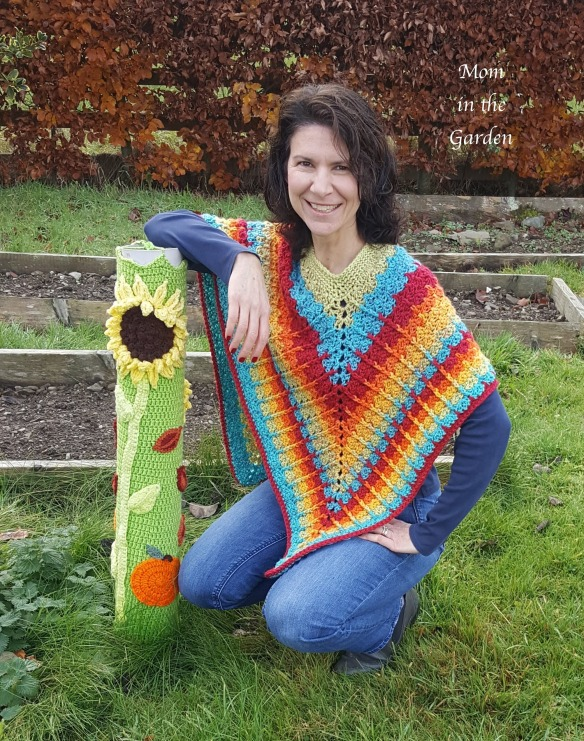 mom in the garden kneeling at flowerbombed pipe in the garden wearing rainbow poncho