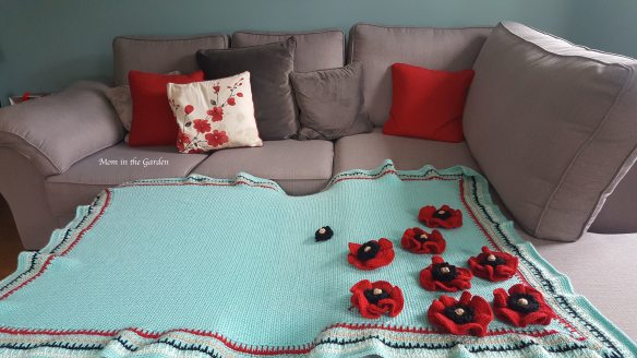 Blue blanket on couch with some flowers